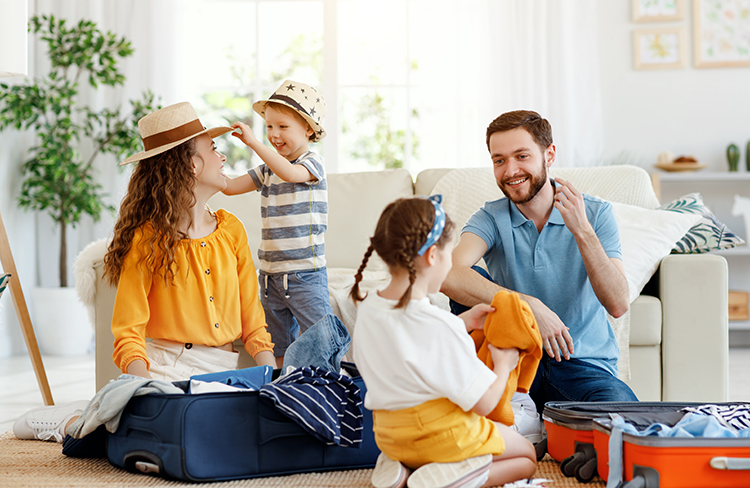 Playful family packing for holiday at home