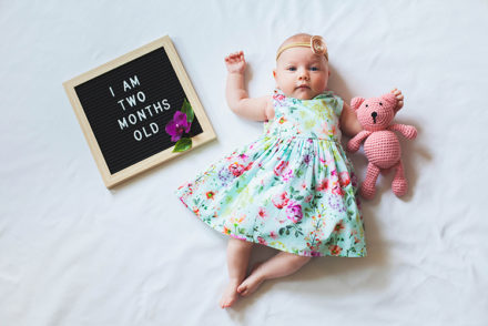 Two months old baby girl wearing floral dress and headband laying near text board and hugging teddy bear.